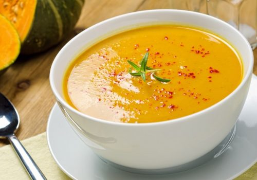 A hot bowl of creamy squash soup with rosemary and paprika.